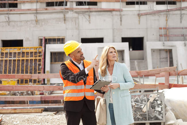 man with hard hat standing with woman on construction site stock