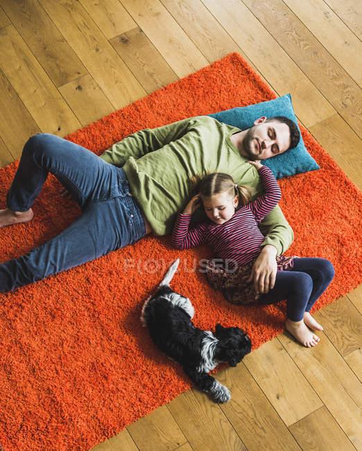 Père et fille couché sur le tapis sur le plancher avec chien — Photo de stock