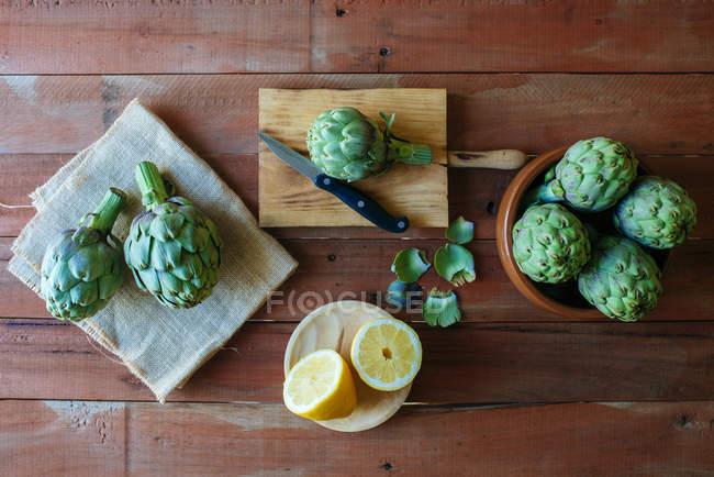 Rohe Artischocken und halbierte Zitrone — Stockfoto