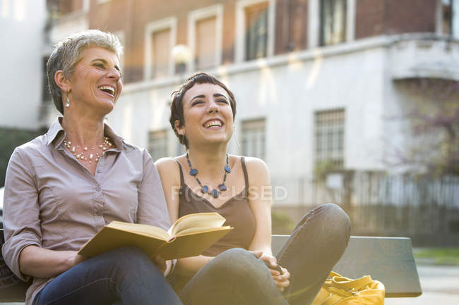 Laughing Mother and adult daughter sitting on bench with book — Stock Photo