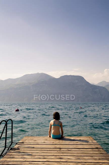 Италия, Бренцоне, Вид сзади на девушку, сидящую на пристани — стоковое фото
