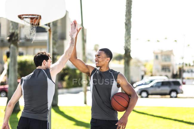 Два молодых человека дают пять на открытой баскетбольной площадке — стоковое фото