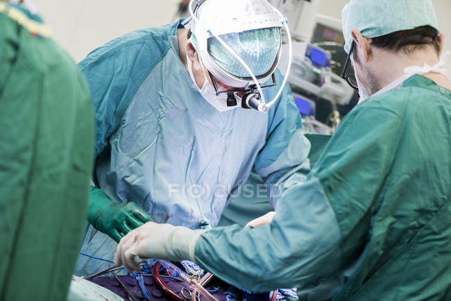Cropped view of heart surgeons during an operation — Stock Photo