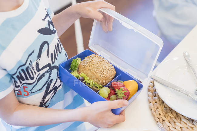 Boy packing lunch box with healthy food — Stock Photo