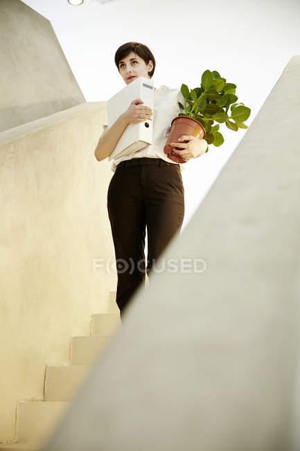 Frau mit Ordner und Topfpflanze stehend auf der Treppe — Stockfoto