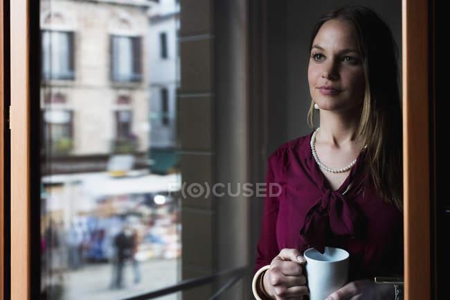 Молода жінка, стоячи за вікном, пити каву — стокове фото