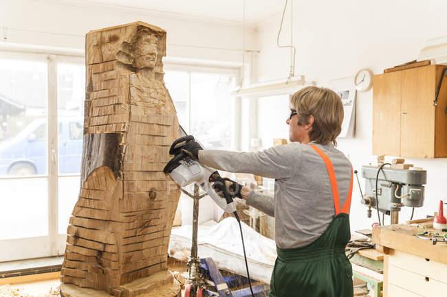 Резчик по дереву в мастерской работает над скульптурой с бензопилой — стоковое фото