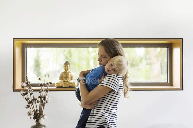 Madre che tiene il figlio a casa — Foto stock