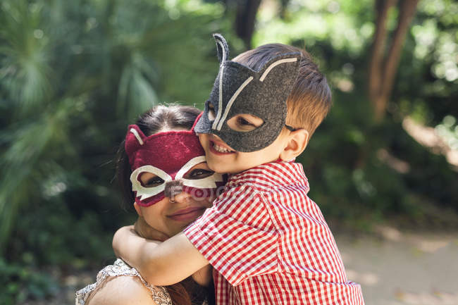 Mother and little son with animal masks playing in the park — Stock Photo