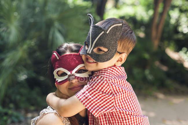 Mère et petit fils avec des masques d'animaux jouant dans le parc — Photo de stock