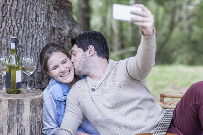 Щасливі молода пара з пікніка з білим вином, беручи за selfie — стокове фото