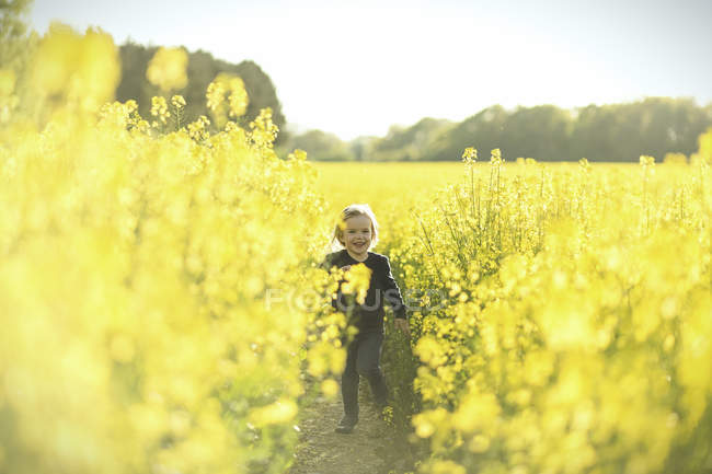 Happy girl running in canola field — Stock Photo