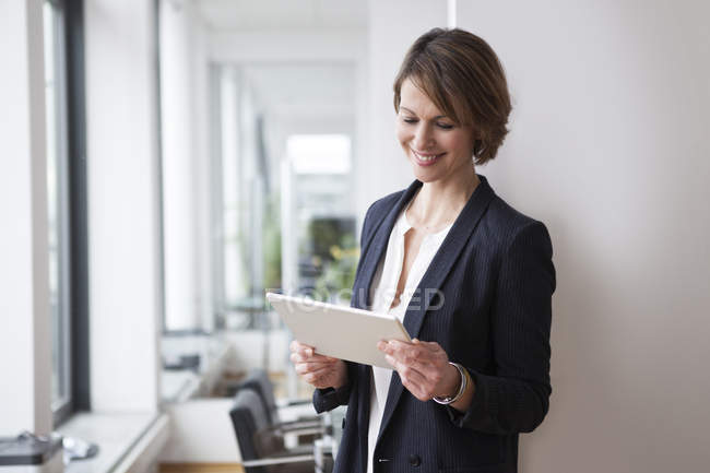 Smiling businesswoman holding digital tablet in office — Stock Photo