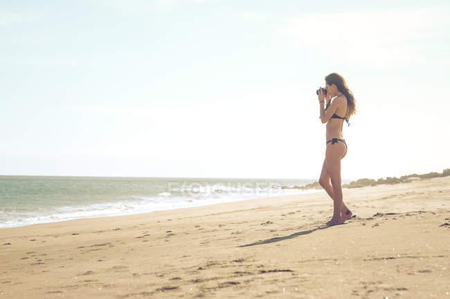 Spagna, Tenerife, giovane donna in piedi sulla spiaggia che scatta una foto — Foto stock
