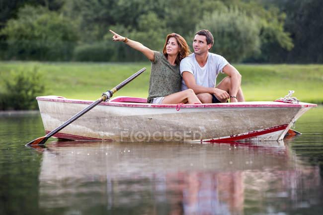 Pareja de jóvenes sentados en un bote de remos en el lago buscando a distancia - foto de stock