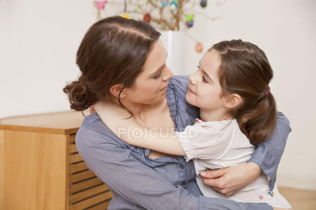 Portrait of mother and daughter hugging each other at home — Stock Photo