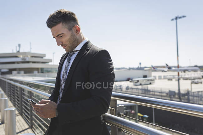 Businessman with cell phone at airport — Stock Photo