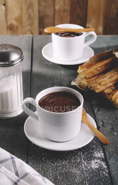Churros avec des tasses de chocolat chaud sur la table — Photo de stock