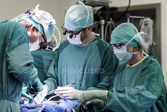 Heart surgeons and operating room nurse during a heart operation — Stock Photo