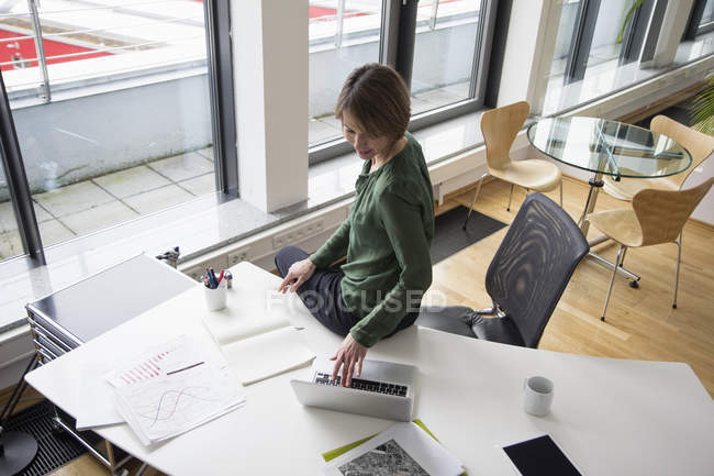 Businesswoman using laptop at office desk — Stock Photo
