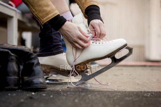 Close-up of woman putting on ice skates — Stock Photo