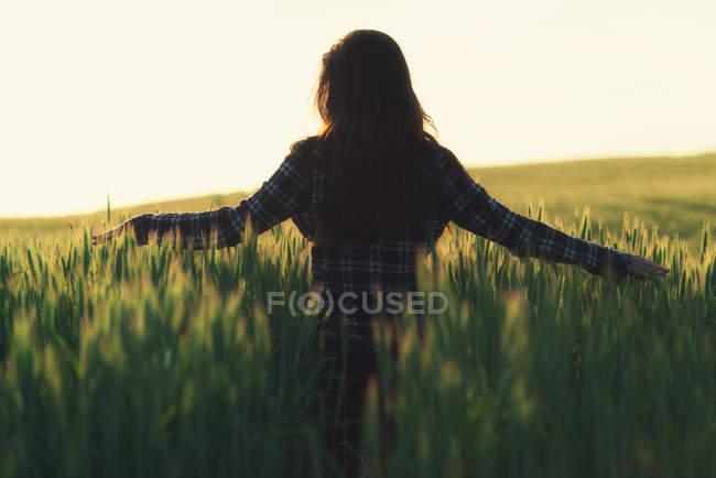 Woman walking in a field raising hands — Stock Photo