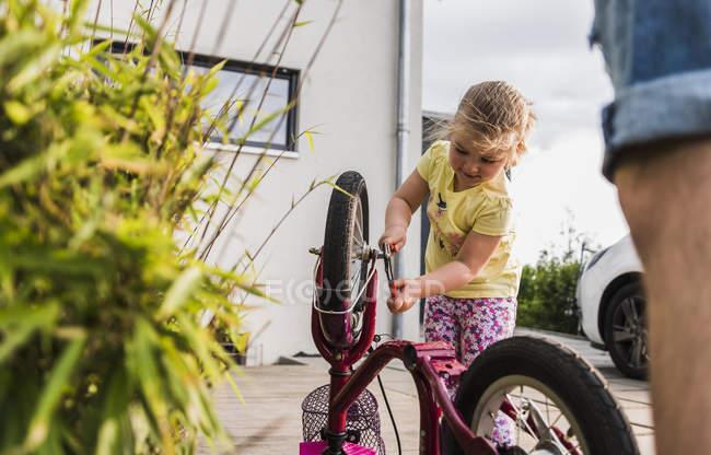Little girl repairing bicycle on street — Stock Photo