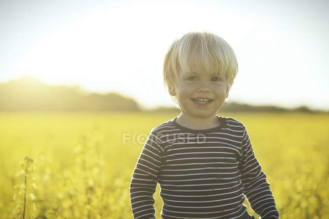 Портрет улыбающегося мальчика в поле канолы — стоковое фото