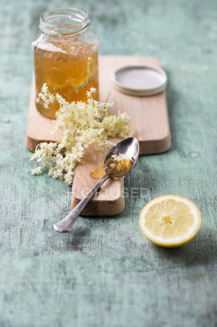 Closeup view of elderflower jelly in jar with spoon, flowers and lemon — Stock Photo