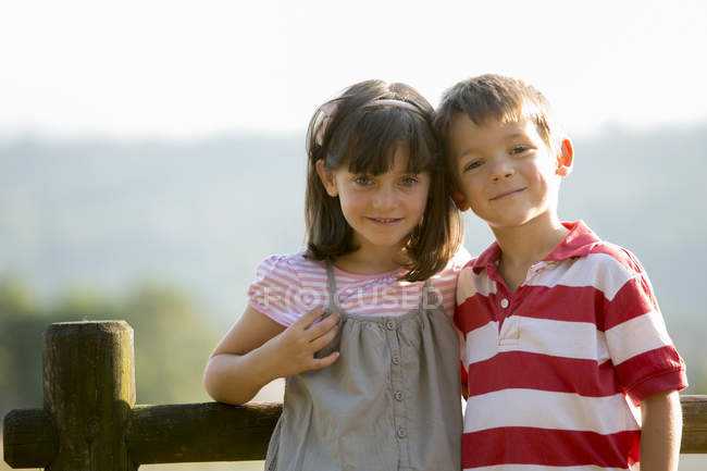 Happy little boy and girl standing face to face in nature — Stock Photo
