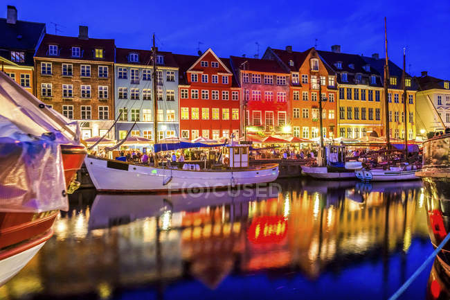 Denmark, Copenhagen, view of historic boats and row of houses at Nyhavn in the evening — Stock Photo