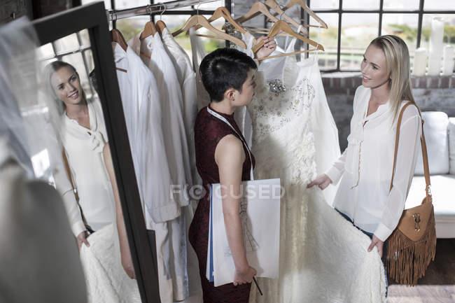 Весільну сукню дизайнер і нареченої, стоячи в весільний магазин — стокове фото