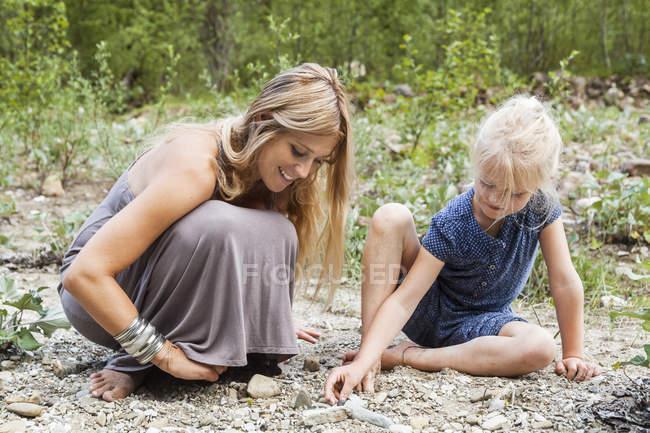 Матері і малою донькою шукає камені в природі — стокове фото