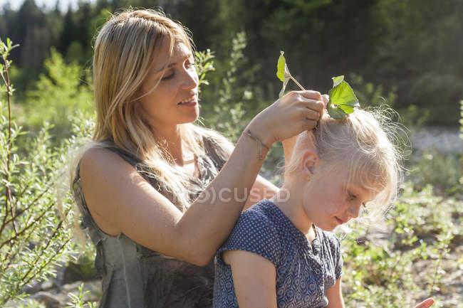 Закрепление мать оставляет в своей дочери волосы — стоковое фото