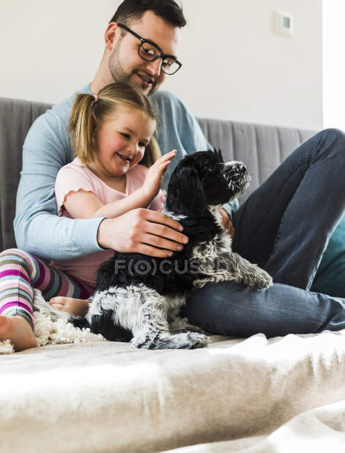 Father and daughter petting dog at home — Stock Photo