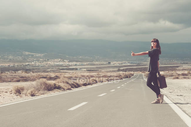 Giovane donna con valigia Autostop su strada — Foto stock