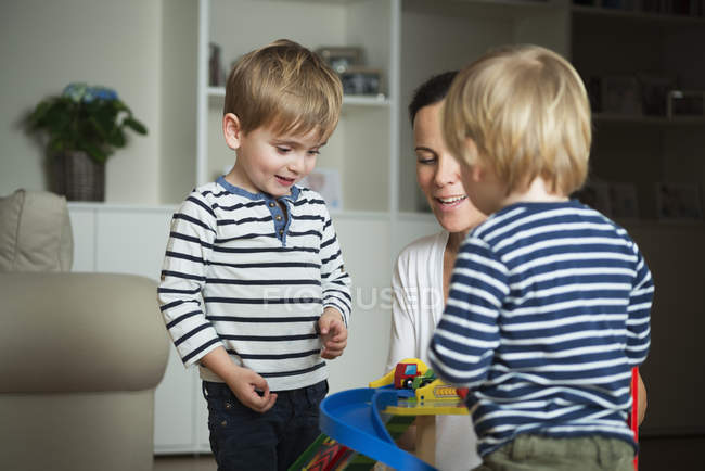 Mother and two little boys playing at home with toys — Stock Photo