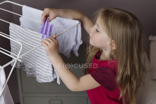 Bambina che appendere la biancheria su un rack di essiccazione — Foto stock