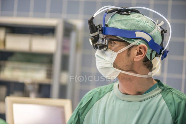 Кардиохирург с головной лампой в операционной — стоковое фото