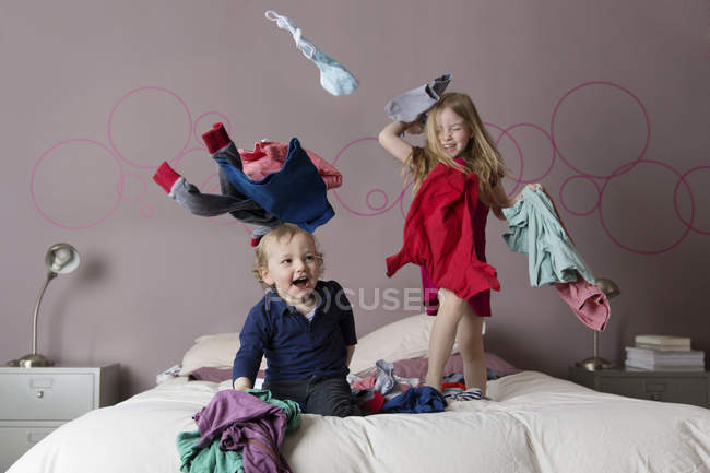 Two laughing siblings playing with laundry on their parents' bed — Stock Photo