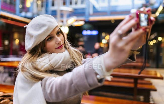 Jeune femme portant selfie prenant béret avec appareil photo numérique — Photo de stock