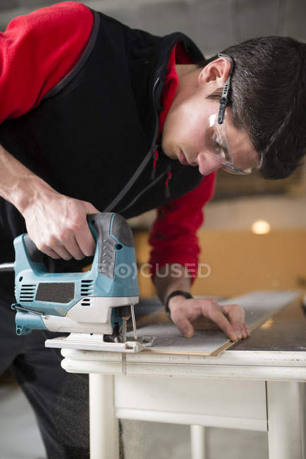 Man cutting laminate floor pieces with a jigsaw — Stock Photo