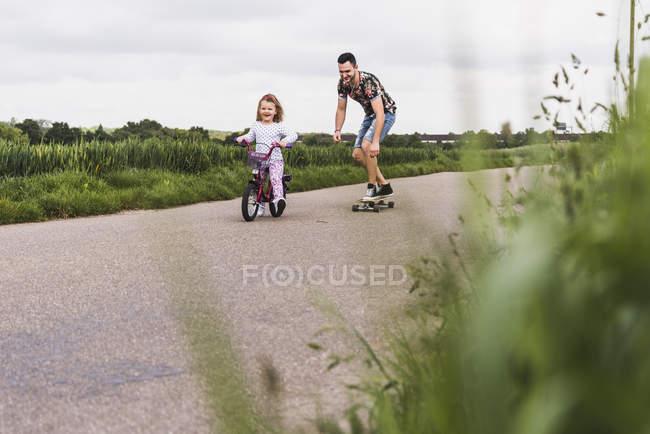 Pai, a filha de acompanhamento skate em bicicleta — Fotografia de Stock