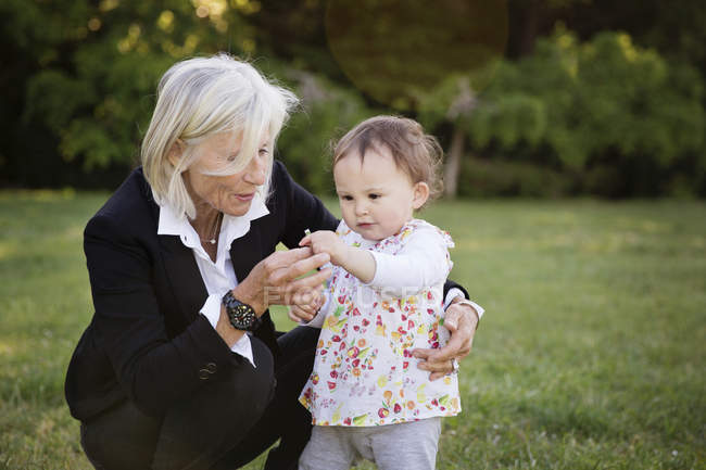 Grandmother and her little granddaughter together in the park — Stock Photo