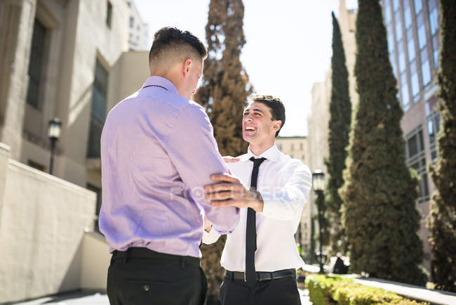 Two businessmen shaking hands in city street — Stock Photo