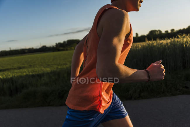 Young man jogging, arm, in the evening light — Stock Photo