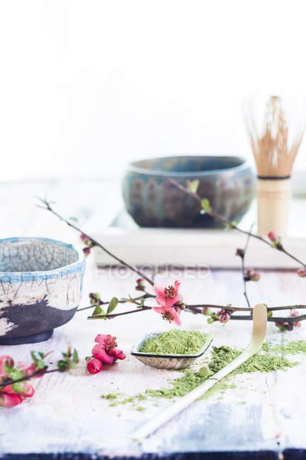 Чашка чая маття с порошком, ложкой, часеном и розовыми цветами — стоковое фото