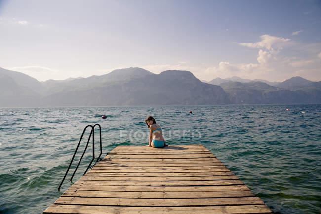 Italy, Brenzone, Rear portrait of girl sitting on jetty — Stock Photo