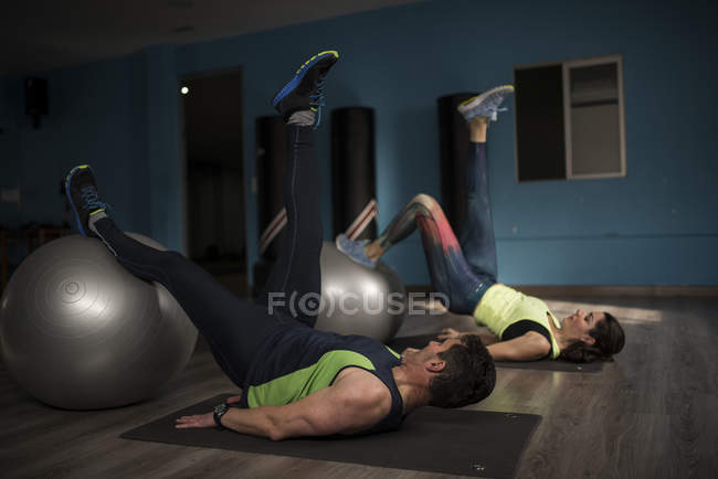 Mature couple training with fitness ball in gym — Stock Photo