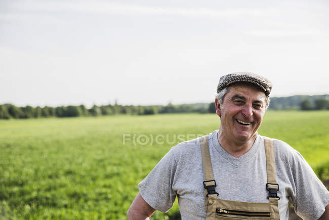 Portrait of smiling farmer at a field — Stock Photo